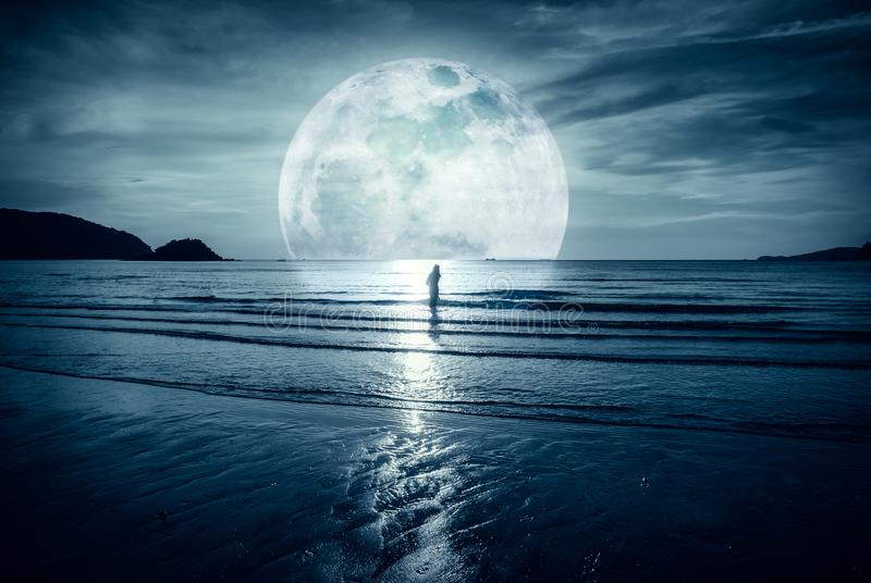 Super moon. Colorful sky with cloud and bright full moon over se. Super moon. Colorful sky with bright full moon over seascape and silhouette of woman standing stock image