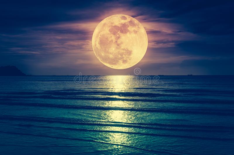 Super moon. Colorful sky with cloud and bright full moon over se. Ascape in the evening. Serenity nature background, outdoor at nighttime. Cross process. The stock photography