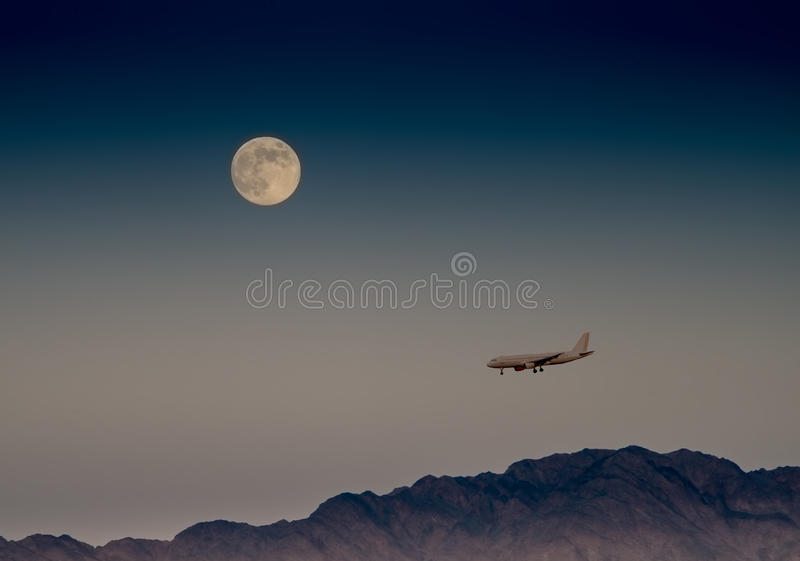 Super moon and landing airplane. The photo was taken during rising the super moon in desert of the Negev, Israel stock photos