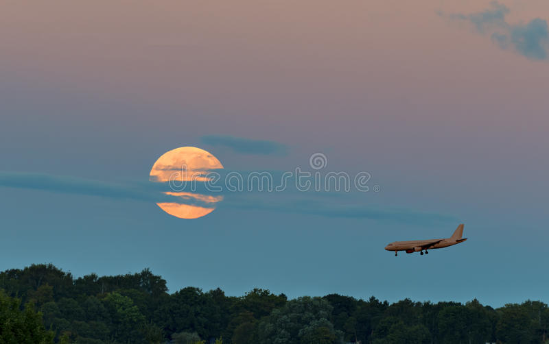 Super moon and landing airplane. The photo was taken during rising the super moon on 15 September, 2015, in Jurmala, Latvia royalty free stock photo