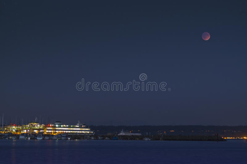 Super moon Lunar eclipse and ferry dock at night. Super moon lunar eclipse and the Washington state ferry terminal in Kingston royalty free stock image