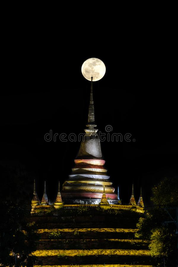 Super moon in night sky and silhouette of ancient pagoda is name stock image