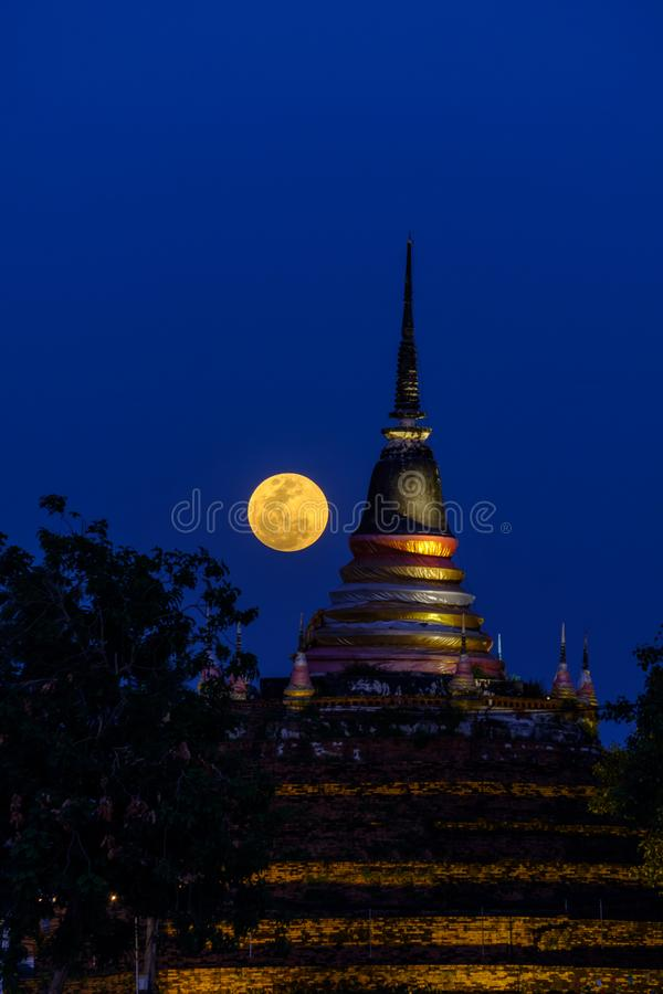 Super moon in night sky and silhouette of ancient pagoda is named Wat Ratchaburana, Phitsanulok in Thailand.  stock photo