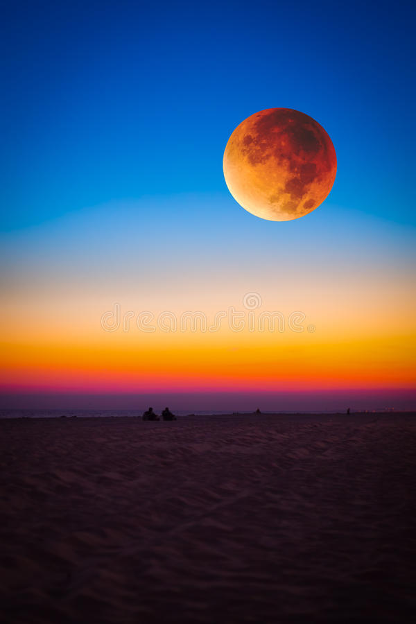 Super Moon. Over colorful sunset beach