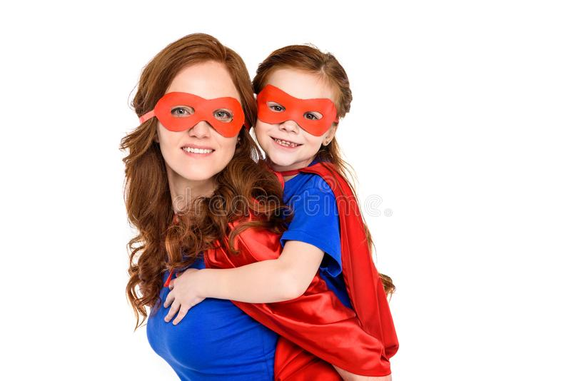 super mother piggybacking adorable daughter in mask and cloak and smiling at camera royalty free stock image