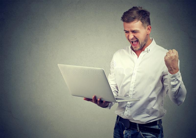 Super opgewekte jonge mens met laptop computer royalty-vrije stock foto's
