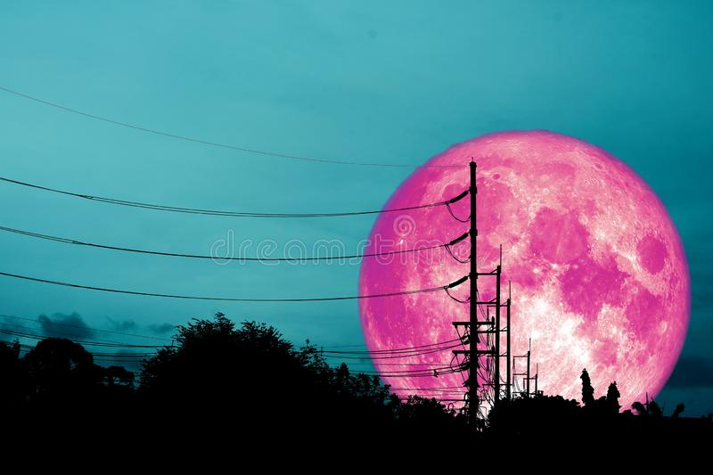 super pink moon floats in the sky above the shadow of an electric pole royalty free stock image