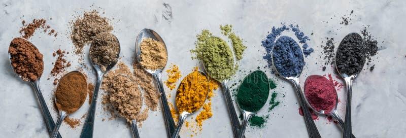 Super powders in spoons - matcha, turmeric, ginger, cocoa, spirulina, chia, cinnamon, black sesame stock images