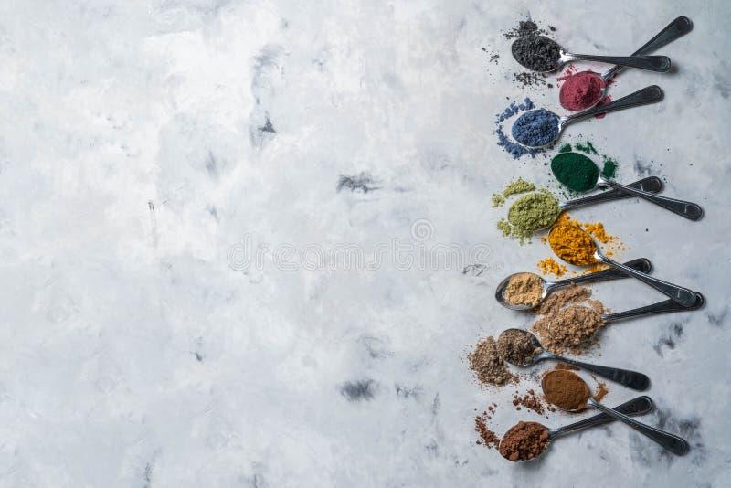 Super powders in spoons - matcha, turmeric, ginger, cocoa, spirulina, chia, cinnamon, black sesame stock photography