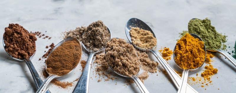 Super powders in spoons - matcha, turmeric, ginger, cocoa, spirulina, chia, cinnamon, black sesame stock photos
