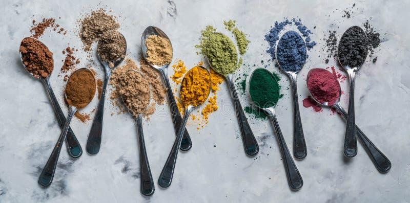 Super powders in spoons - matcha, turmeric, ginger, cocoa, spirulina, chia, cinnamon, black sesame stock image