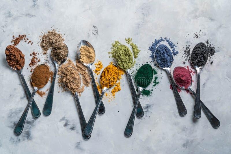 Super powders in spoons - matcha, turmeric, ginger, cocoa, spirulina, chia, cinnamon, black sesame stock photo