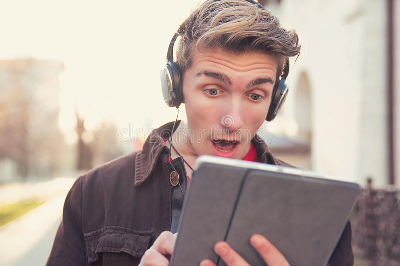 Super shocked man using tablet stock photography