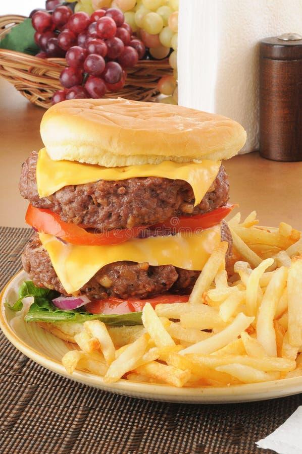 Super sized hamburger with fries stock image
