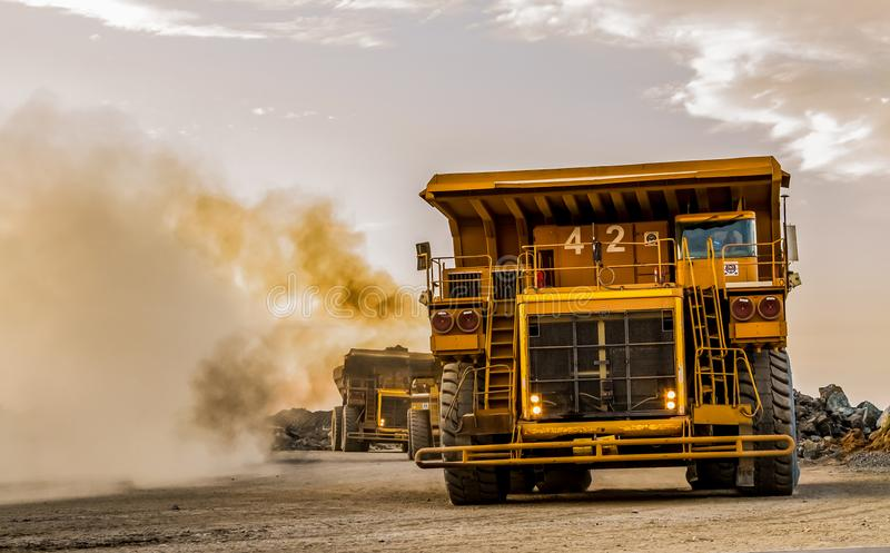 Super Large mining rock dump trucks transporting Platinum ore for processing stock images