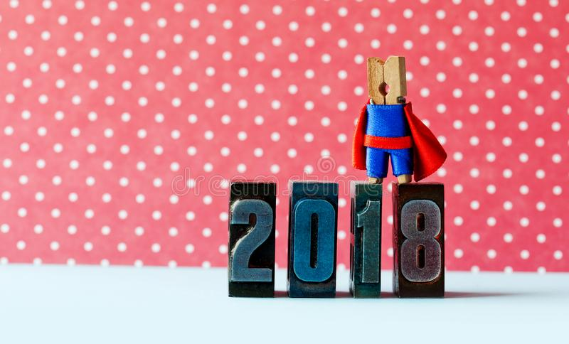 Super successful 2018 new year card. Brave superhero leader posing on vintage letterpress digits. Beautiful clothespin royalty free stock photos