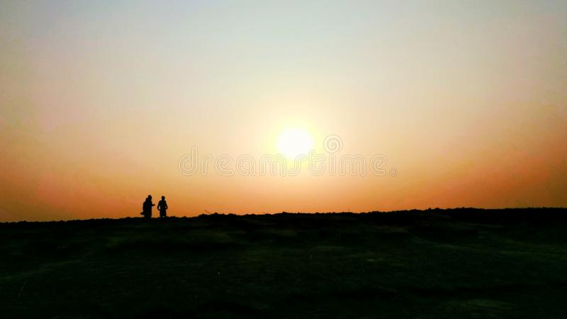 Super Sunset. Two person talking during sunset royalty free stock photos