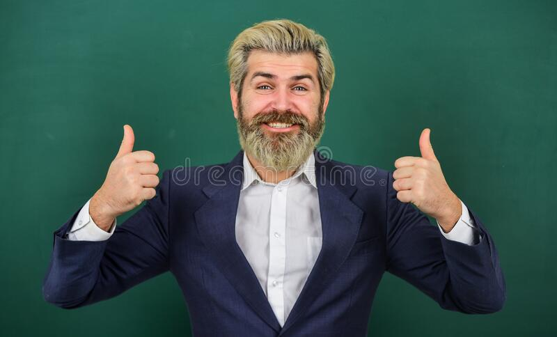 Super teacher. Happy man give thumbs ups at chalkboard. Senior professor smile gesturing thumbs ups. Approval and. Appreciation. Thumbs ups. Hand signs. Thumbs stock image