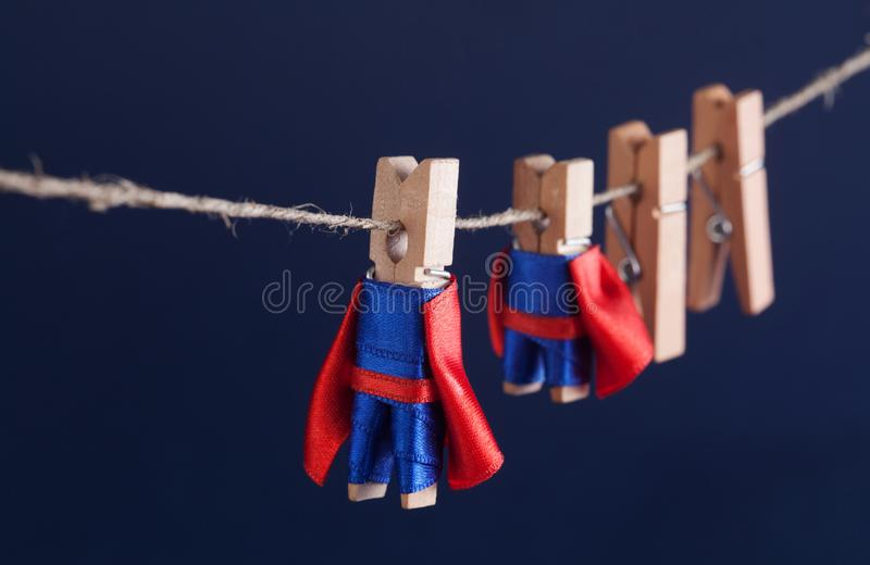 Super team concept photo with clothespin superheroes in blue suit and red cape. Big small powerful heroes. Dark. Background. soft focus. macro view, shallow stock photo