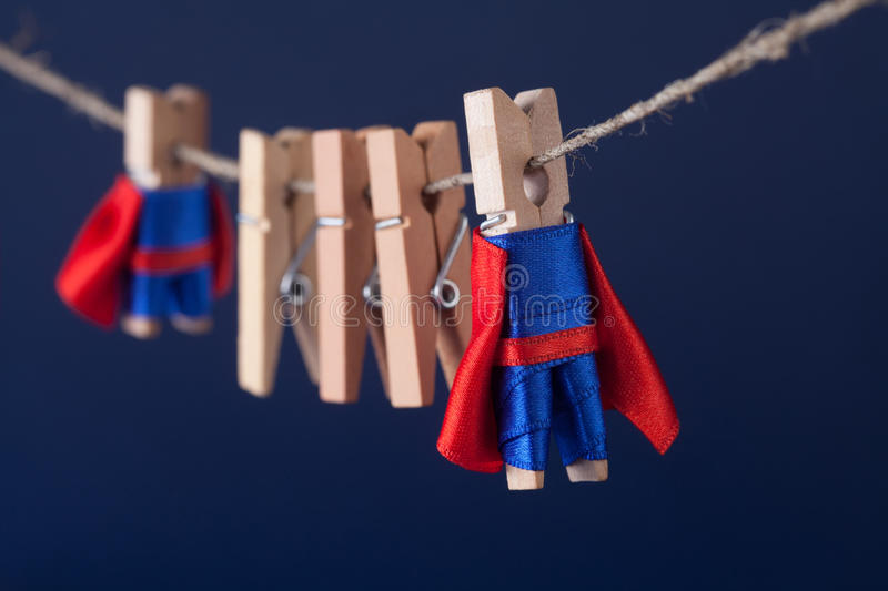 Super team concept photo with clothespin superheroes in blue suit and red cape. Big small powerful heroes. Dark. Background. soft focus. macro view royalty free stock image
