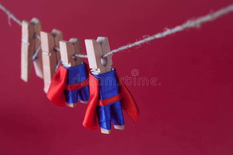 Super team leadership concept photo with clothespin superheroes in blue suit and red cape. Big small powerful heroes. Hanging clothesline. Pink background royalty free stock image
