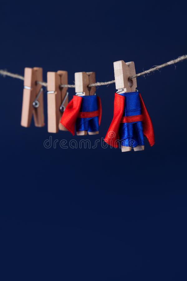 Super team poster concept. Photo clothespin superheroes in blue suit and red cape. Big small powerful heroes. Dark. Background. soft focus. macro view, shallow stock images