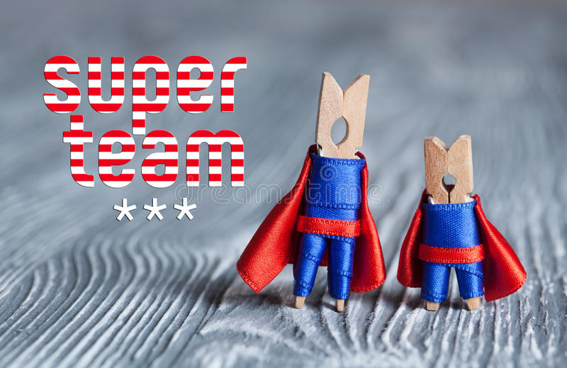 Super teamconcept Wasknijperpin superheroes in blauw kostuum en rode kaap Grijze houten abstracte ontwerpachtergrond Macro royalty-vrije stock foto's