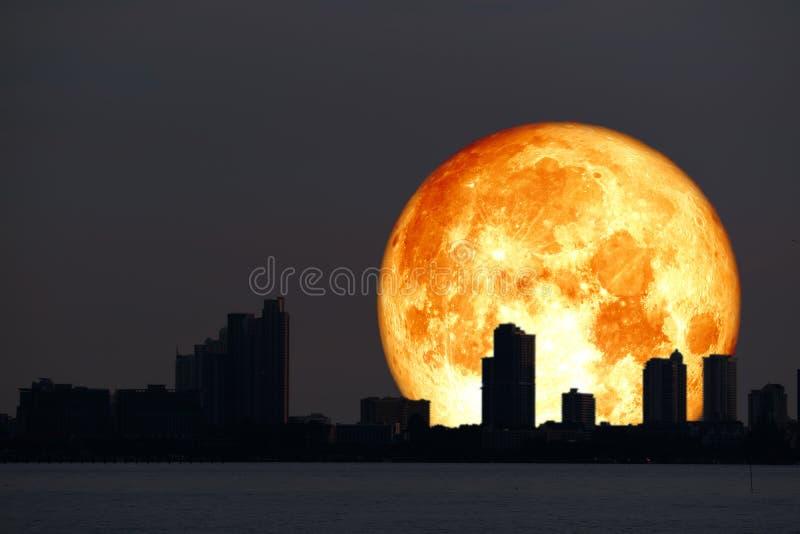 super van de de maanplaneet van het bloedhooi achter het silhouetstad en nachthemel royalty-vrije stock foto's