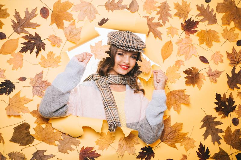 It is super warm. Fall look of vogue model. Fashion girl look through torn paper with autumn leaves. Pretty woman wear royalty free stock photo