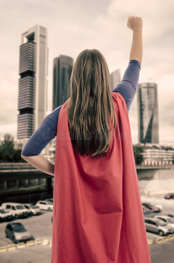Super woman hero with red cape and mask in Madrid. Vintage color. Super woman hero with red cape and mask in Madrid, Spain. Vintage color royalty free stock photography