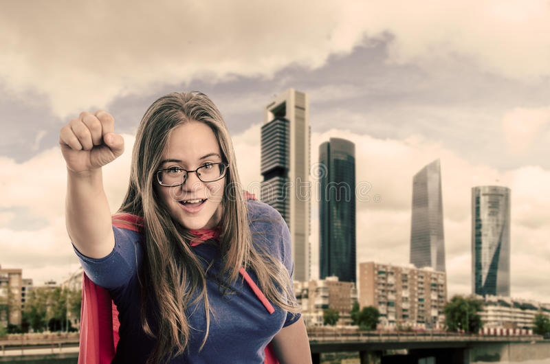 Super woman hero with red cape and mask in Madrid. Vintage color. Super woman hero with red cape and mask in Madrid, Spain. Vintage color stock photo