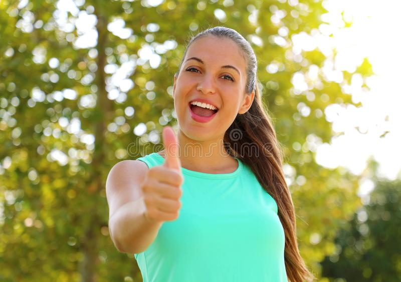 Super woman! Portrait of winner girl showing thumb up. Positive smiling fitness healthy woman outdoor stock images
