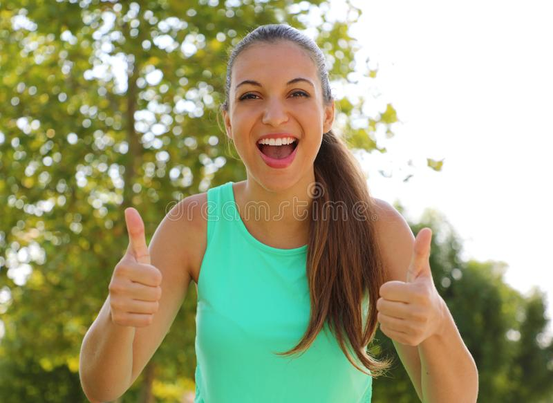Super woman! Portrait of winner girl showing thumbs up. Positive smiling fitness healthy woman outdoor royalty free stock photos