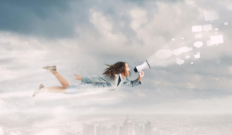 Super woman. Young businesswoman with megaphone flying high in sky stock photo