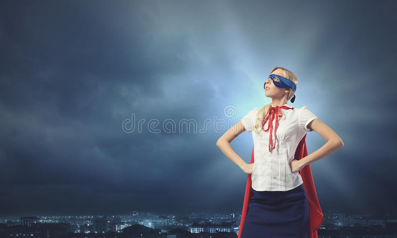Super woman. Young confident woman in red cape and mask royalty free stock images