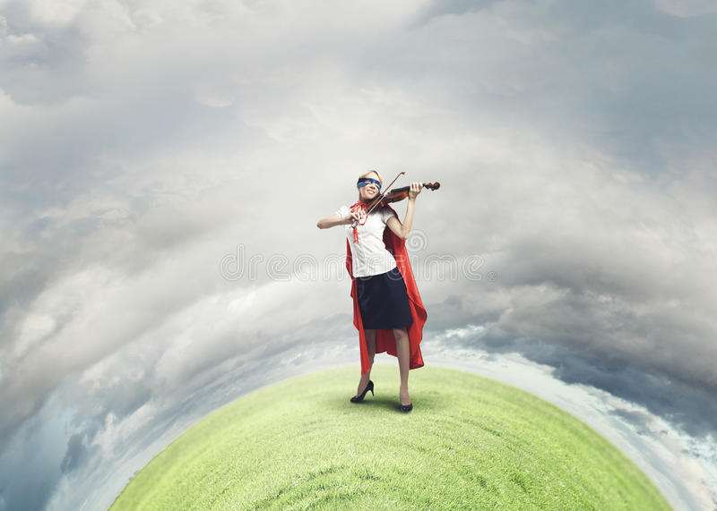Super woman. Young confident woman in red cape and mask playing violin royalty free stock photos