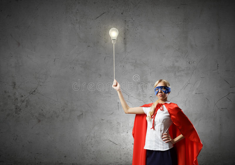 Super woman. Young woman in super hero costume with bulb balloon in hand royalty free stock images
