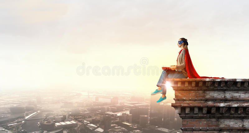 She is super woman. Young thoughtful woman in red cape and mask on building roof read book royalty free stock photography