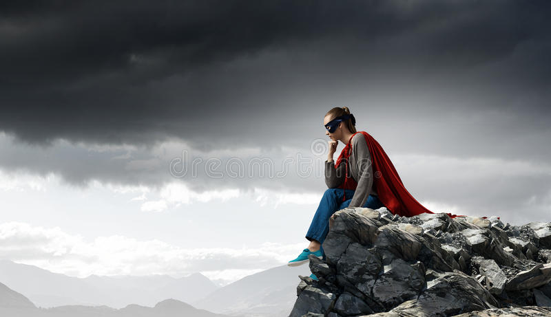 She is super woman. Young thoughtful woman in red cape and mask on rock top royalty free stock photo