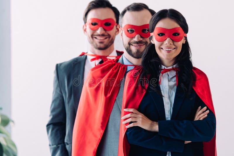 super zakenlui in maskers en kaap die camera bekijken stock afbeelding