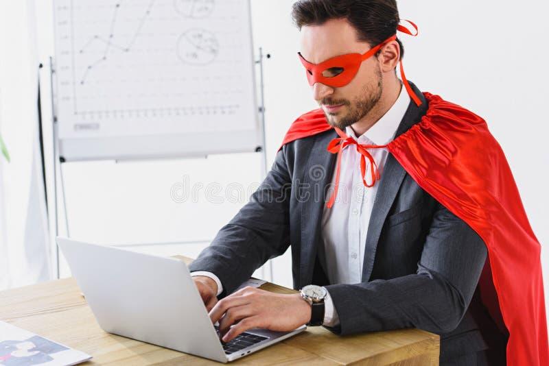 super zakenman in masker en kaap die met laptop werken stock fotografie