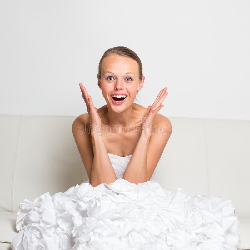 Superaufgeregtes, herrlich, Braut, die auf einer Couch sitzt stockfotos