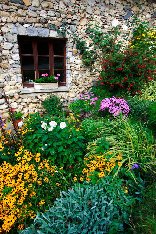 Superb garden. In the countryside. Red, orange, pink, green, yellow and white flowers in front of an old stoned-built house stock photo