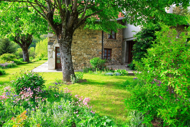 Superb garden and old house. Superb green garden and stone-built house in the the french countryside (chartreuse). Photo for a book cover. Home sweet home stock image