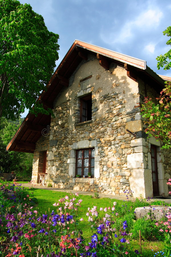 Superb stone-built house and garden. Superb old house and garden in the natural park of chartreuse (france) with flowers at first plan. Home sweet home. Real royalty free stock images