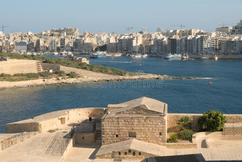 Valletta, Malta, August 2019. Buildings on the city wall against the backdrop of the bay and cityscape. Superb view of the simple old commercial buildings on royalty free stock photos