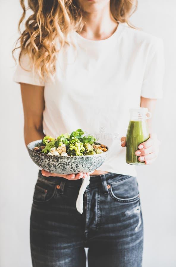 Superbowl des Frauenholding-strengen Vegetariers und grüner Smoothie in den Händen stockbilder