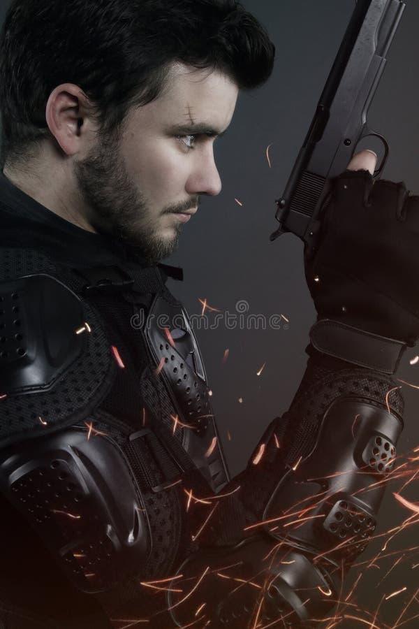 Superbullen - brauner Mann, der mit einem Gewehr aufwirft stockbild
