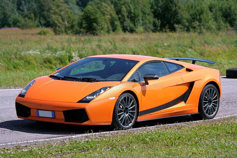 Supercar orange sur un champ de courses photographie stock