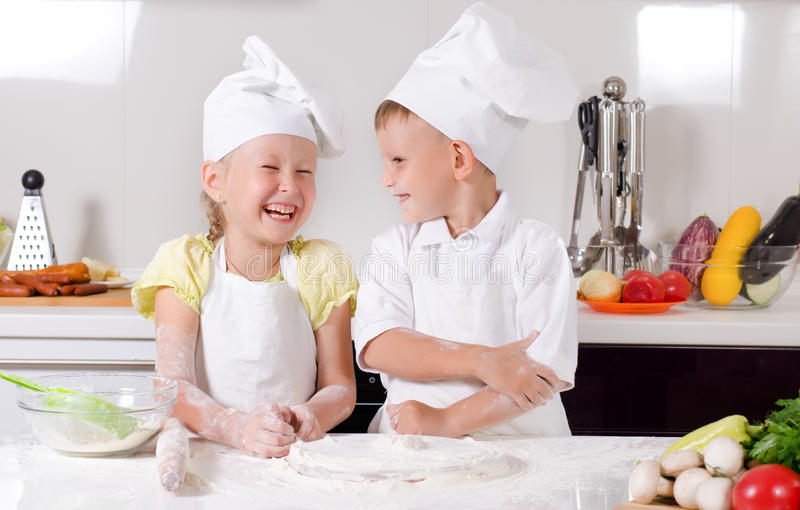Supercilious little boy chef. Standing proudly with folded arms looking down on a cute little girl also in chefs uniform royalty free stock photography